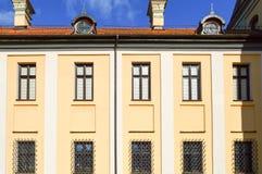 Όμορφα κίτρινα ιστορικά μεσαιωνικά ευρωπαϊκά κτήρια χαμηλός-ανόδου με ένα κόκκινο αέτωμα στεγών κεραμιδιών και ορθογώνια παράθυρα στοκ εικόνα με δικαίωμα ελεύθερης χρήσης