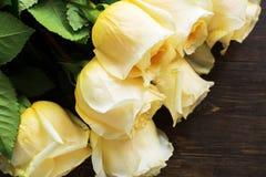 Όμορφα κίτρινα τριαντάφυλλα πέρα από το ξύλινο υπόβαθρο grunge στοκ φωτογραφία με δικαίωμα ελεύθερης χρήσης