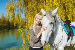 Όμορφα και φυσικά νέα έξοδα γυναικών κάποτε με το άσπρο άλογό της Στοκ Φωτογραφία