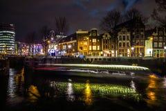 Όμορφα κανάλια πόλεων νύχτας του Άμστερνταμ με την κίνηση της βάρκας επιβατών Στοκ Φωτογραφία