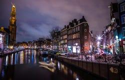 Όμορφα κανάλια πόλεων νύχτας του Άμστερνταμ με την κίνηση της βάρκας επιβατών Στοκ Εικόνες