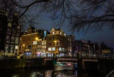 Όμορφα κανάλια πόλεων νύχτας του Άμστερνταμ με την κίνηση της βάρκας επιβατών Στοκ εικόνες με δικαίωμα ελεύθερης χρήσης