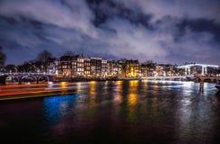 Όμορφα κανάλια πόλεων νύχτας του Άμστερνταμ με την κίνηση passanger της βάρκας Στοκ Εικόνα