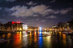 Όμορφα κανάλια πόλεων νύχτας του Άμστερνταμ με την κίνηση passanger της βάρκας Στοκ Εικόνες