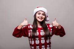 Όμορφα καπέλο santa ένδυσης κοριτσιών πρότυπα και πουλόβερ Χριστουγέννων με τη χειρονομία okey Στοκ Εικόνες