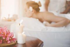 Όμορφα κεριά στον πίνακα στο δωμάτιο SPA με την όμορφη γυναίκα στο σαλόνι SPA και το υπόβαθρο μασέρ ή θεραπόντων μασάζ στοκ φωτογραφία