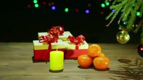 Όμορφα κιβώτια με τα δώρα δίπλα στο χριστουγεννιάτικο δέντρο σε ένα μαύρο υπόβαθρο με τα φω'τα απόθεμα βίντεο