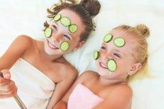 Όμορφα κορίτσια με την του προσώπου μάσκα του αγγουριού στοκ φωτογραφία