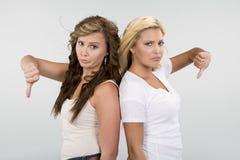 2 όμορφα κορίτσια με τους αντίχειρες κάτω Στοκ Εικόνες