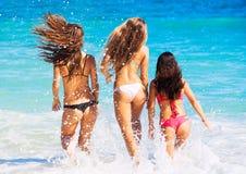 Όμορφα κορίτσια που έχουν τη διασκέδαση που περπατά στην παραλία Στοκ Εικόνες