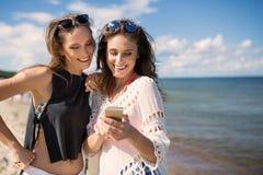 Όμορφα κορίτσια που εξετάζουν το τηλέφωνο στο χαμόγελο παραλιών Στοκ Φωτογραφία