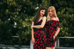 Όμορφα κορίτσια που θέτουν για το φωτογράφο Δύο αδελφές στο μαύρο και κόκκινο φόρεμα Χαμόγελο, ηλιόλουστη ημέρα, καλοκαίρι Στοκ εικόνες με δικαίωμα ελεύθερης χρήσης