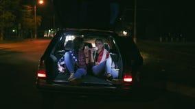 Όμορφα κορίτσια που κάθονται στον ανοικτό κορμό του αυτοκινήτου, που μιλούν και που τρώνε τα burgers κατά τη διάρκεια της νύχτας  απόθεμα βίντεο