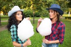 Όμορφα κορίτσια στα καπέλα κάουμποϋ που τρώνε την καραμέλα βαμβακιού στοκ εικόνα με δικαίωμα ελεύθερης χρήσης