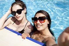 Όμορφα κορίτσια στα μαγιό που έχουν τη διασκέδαση στη λίμνη r στοκ εικόνα