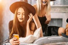 Όμορφα κορίτσια στα μαύρα φορέματα και καπέλα μαγισσών που χρησιμοποιούν το έξυπνο τηλέφωνο Στοκ Εικόνα