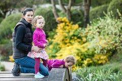 Όμορφα κορίτσια στα ρόδινα σακάκια και ζωηρόχρωμες φούστες με τη μητέρα στη γέφυρα Στοκ φωτογραφία με δικαίωμα ελεύθερης χρήσης