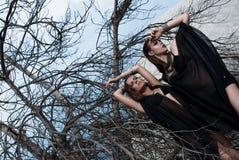 Όμορφα κορίτσια brunette με το φωτεινό makeup και τα ρόδινα χείλια που φορούν τη μαύρη τοποθέτηση υπαίθρια στον μπλε θερινό ουραν στοκ εικόνα