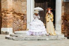 Όμορφα κοστούμια αριστοκρατών μπροστά από τον παλαιούς τουβλότοιχο και την πόρτα στη Βενετία, Ιταλία στοκ εικόνες