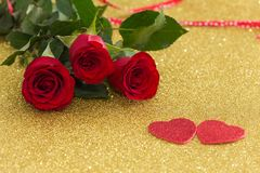 Όμορφα κόκκινα τριαντάφυλλα με τις διακοσμητικές καρδιές σε ένα χρυσό υπόβαθρο Στοκ εικόνες με δικαίωμα ελεύθερης χρήσης