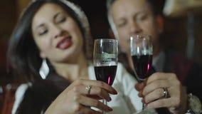 Όμορφα λατινικά γυαλιά κουδουνίσματος ζευγών με το κόκκινο κρασί στην ημερομηνία στην περιστασιακή εξάρτηση στο σπίτι Ζεύγος που  απόθεμα βίντεο