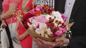 Όμορφα λουλούδια εκμετάλλευσης επιχειρηματιών Νεόνυμφος σε ένα κοστούμι που κρατά μια ανθοδέσμη των λουλουδιών Γαμήλια μπουτονιέρ φιλμ μικρού μήκους