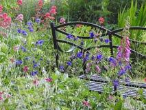 Όμορφα λουλούδια κήπων εξοχικών σπιτιών με τον πάγκο μετάλλων Στοκ Φωτογραφίες