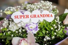 Όμορφα λουλούδια στο θολωμένο υπόβαθρο Ανθοδέσμη των άσπρων και πορφυρών λουλουδιών Ευτυχής ημέρα παππούδων και γιαγιάδων χαιρετι στοκ εικόνα