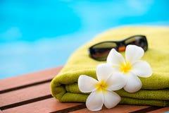 όμορφα λουλούδια plumeria και μια πετσέτα υφασμάτων σε έναν αργόσχολο Στοκ Φωτογραφίες