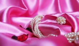 Όμορφα μαργαριτάρια σε ένα υπόβαθρο του ρόδινου μεταξιού Μόδα & ύφος Περιδέραιο και σκουλαρίκια Στοκ Εικόνες