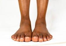 Όμορφα μαύρα θηλυκά επίπεδα πόδια με το ομαλό δέρμα Υγιές μωρό ποδιών γυναικών αφροαμερικάνων Πόδια του μωρού γυμνά που απομονώνε στοκ εικόνες