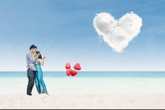 Όμορφα μπαλόνια καρδιών εκμετάλλευσης ζευγών στην παραλία στοκ φωτογραφίες