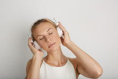 Όμορφα νέα ακουστικά ακούσματος γυναικών πορτρέτου Ονειρεμένος μουσικής υπόβαθρο χρώματος φορέων κενό κίτρινο Το όμορφο κορίτσι α Στοκ Φωτογραφίες