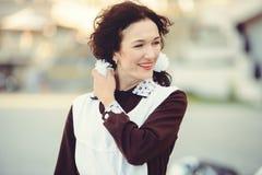 Όμορφα νέα γυναίκα, hairstyle και τόξα υπαίθρια με μια μοτοσικλέτα Ευτυχής και υγιής που ντύνεται σε μια σοβιετική σχολική στολή  Στοκ Εικόνες