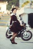 Όμορφα νέα γυναίκα, hairstyle και τόξα υπαίθρια με μια μοτοσικλέτα Ευτυχής και υγιής που ντύνεται σε μια σοβιετική σχολική στολή  Στοκ Φωτογραφία