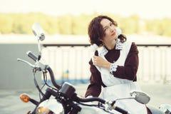Όμορφα νέα γυναίκα, hairstyle και τόξα υπαίθρια με μια μοτοσικλέτα Ευτυχής και υγιής που ντύνεται σε μια σοβιετική σχολική στολή  Στοκ εικόνες με δικαίωμα ελεύθερης χρήσης