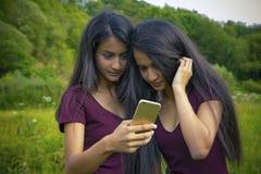 Όμορφα νέα κορίτσια διδύμων που κάνουν selfie Στοκ Εικόνες