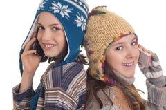 Όμορφα νέα κορίτσια στα θερμά χειμερινά ενδύματα που μιλούν στη Mobil Στοκ Εικόνες