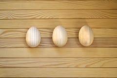 Όμορφα ξύλινα αυγά Πάσχας σε ένα ξύλινο υπόβαθρο Στοκ Εικόνες