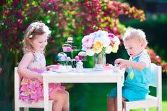 Όμορφα παιδιά που έχουν τη διασκέδαση στο κόμμα τσαγιού κήπων Στοκ Φωτογραφίες