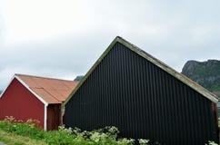 Όμορφα παλαιά σπίτια αλιευτικών σκαφών δίπλα στο θερινό φιορδ με το υπόβαθρο βουνών Στοκ εικόνες με δικαίωμα ελεύθερης χρήσης