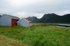 Όμορφα παλαιά σπίτια αλιευτικών σκαφών δίπλα στο θερινό φιορδ με το υπόβαθρο βουνών Στοκ Εικόνες