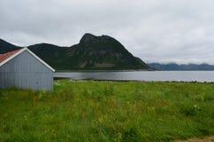 Όμορφα παλαιά σπίτια αλιευτικών σκαφών δίπλα στο θερινό φιορδ Στοκ Φωτογραφίες