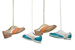 Όμορφα παπούτσια γυναικών χρώματος που κρεμούν στις δαντέλλες με το απομονωμένο λευκό στοκ εικόνες με δικαίωμα ελεύθερης χρήσης
