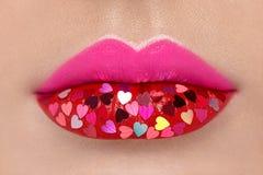 Όμορφα παχουλά ρόδινα χείλια με τις κολλημένες καρδιές στοκ φωτογραφία