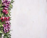Όμορφα πολύχρωμα λουλούδια freesya με τα πράσινα σύνορα φύλλων, θέση για τοπ άποψη υποβάθρου κειμένων την ξύλινη αγροτική Στοκ Φωτογραφία