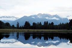 Όμορφα πράσινα δασικά υποβάθρου μπλε σύννεφα και refection βουνών άσπρα στη λίμνη Στοκ Εικόνα