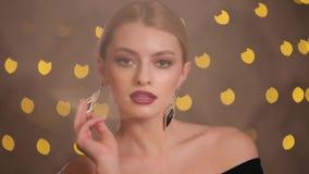 Όμορφα πρότυπα παιχνίδια μόδας με τα σκουλαρίκια πολυτέλειάς της, σε αργή κίνηση φιλμ μικρού μήκους