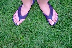 Όμορφα πόδια γυναικών στις θερινές παντόφλες στην πράσινη χλόη, πόδι wom Στοκ φωτογραφία με δικαίωμα ελεύθερης χρήσης
