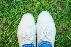Όμορφα πόδια στη χλόη σε ένα πάρκο στη φύση στοκ φωτογραφία